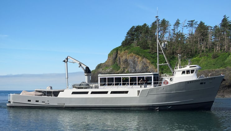Starboard side of silver-and-white, 2-deck Alaska small ship Kruzof Explorer, cruising on a sunny day.