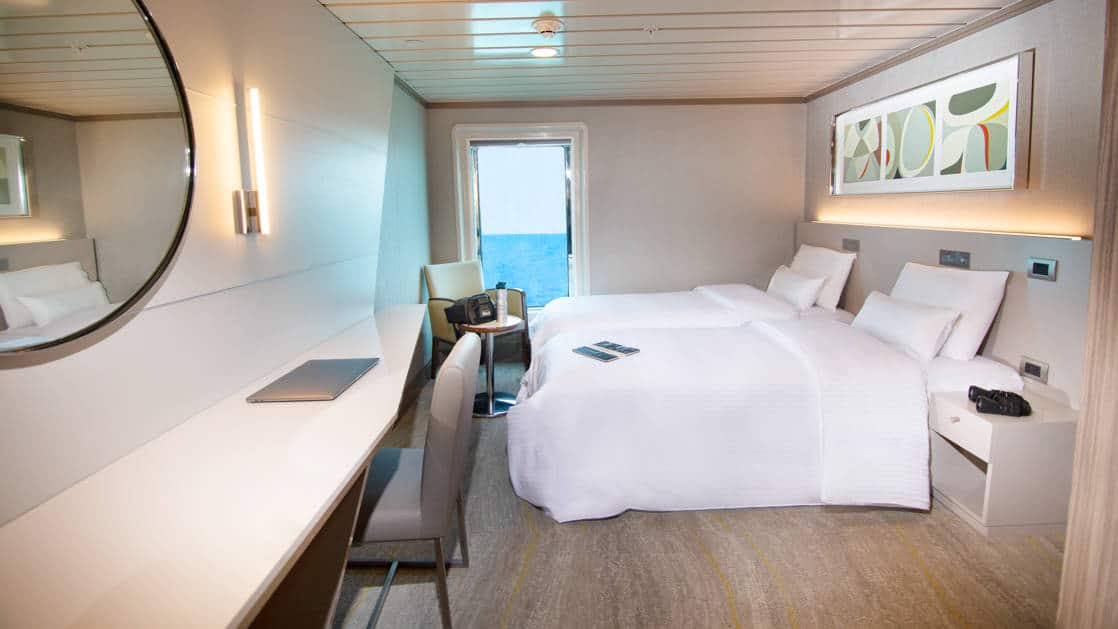 Spacious room aboard the la pinta galapagos with two twin beds, desk and door.
