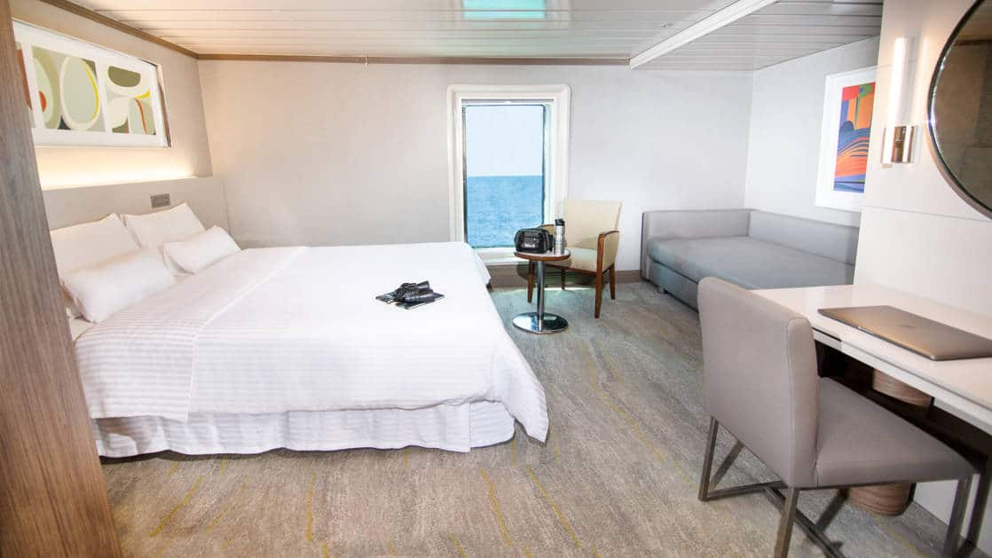 Spacious room aboard the la pinta galapagos with large bed, desk, and sofa.