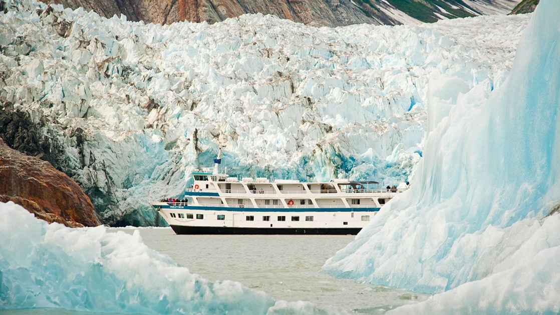 Small ship Admiralty Dream cruises Glacier Bay National Park among giant icy blue crystal glaciers in Alaska.