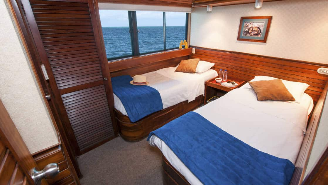 Letty stateroom Dolphin deck cabin with 2 twin beds, large picture window, closet, nightstand and reading light.