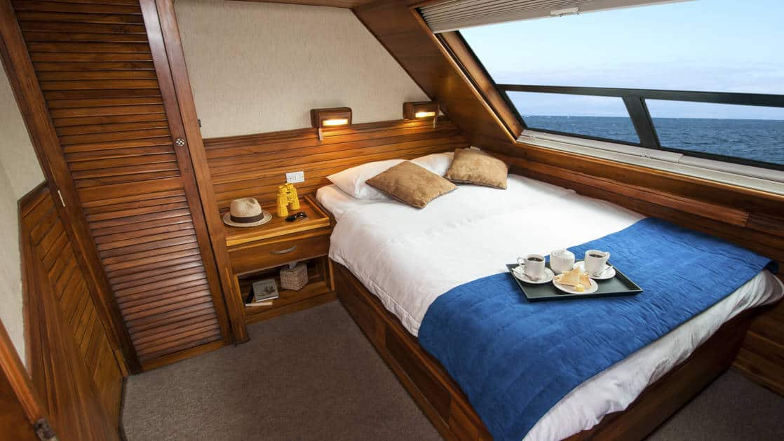 Letty stateroom single cabin with double bed, extra large picture window, nightstand, reading light and closet.