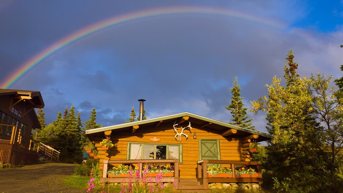 A rainbow arches over one of the cabins at Camp Denali, a historic wilderness lodge with deep ties to the national park in Alaska