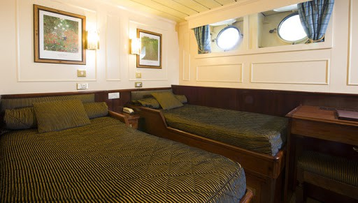 Lord of the Glens Category 1 stateroom with 2 single beds, nightstand, reading lights and 2 portholes.