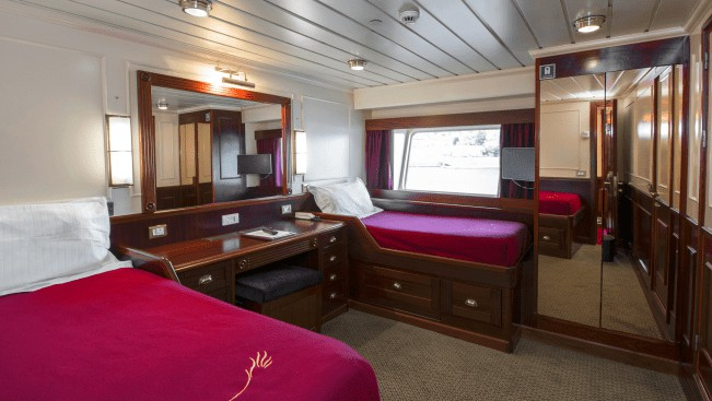 Lord of the Glens Category 2 stateroom with 2 twin beds, dresser, closet, reading lights and large window.