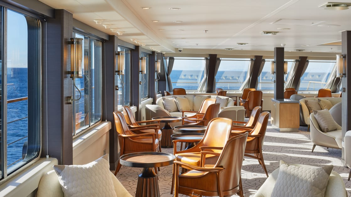lounge area with tan leather accent chairs, grey upholstered love seats and wide wrap around windows aboard Magellan Explorer luxury Antarctica expedition ship