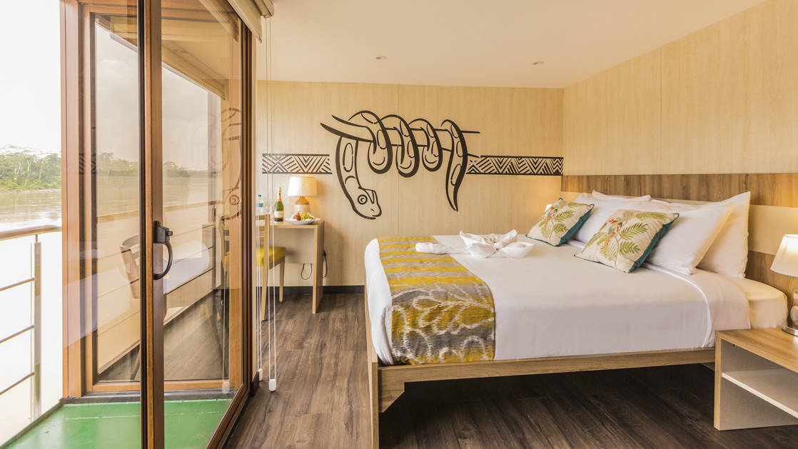 Deluxe Cabin aboard Manatee Amazon Explorer with a large double bed, floor to ceiling windows and sliding glass door,