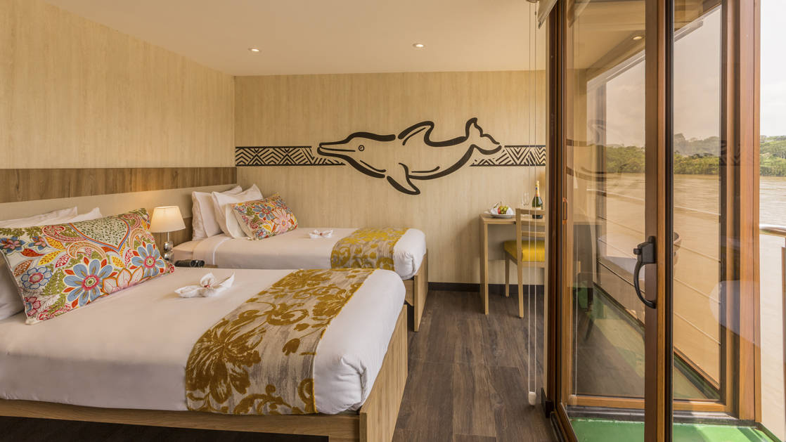 Deluxe Twin aboard Manatee Amazon Explorer with floor to ceiling windows, sliding glass door out to private balcony, nightstand and reading lights.
