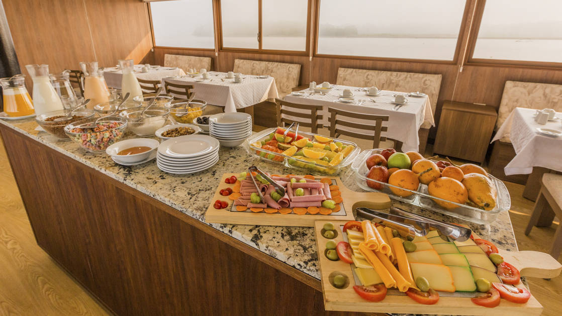 Manatee Amazon Explorer dining room buffet table with assorted foods and large floor to ceiling windows.