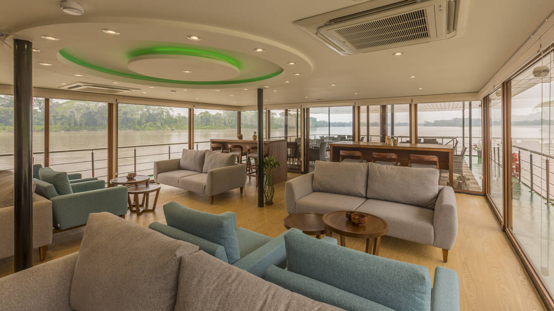Manatee Amazon Explorer lounge with couches, tables, bar and floor to ceiling windows.