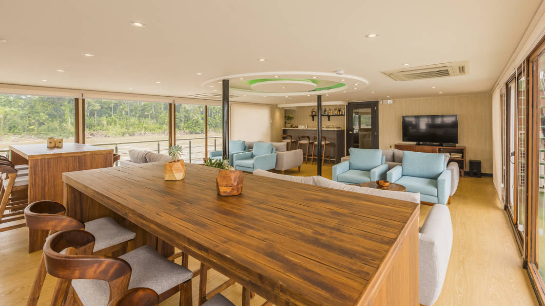 Manatee Amazon Explorer lounge with large table, TV, floor to ceiling windows, couches and tables.
