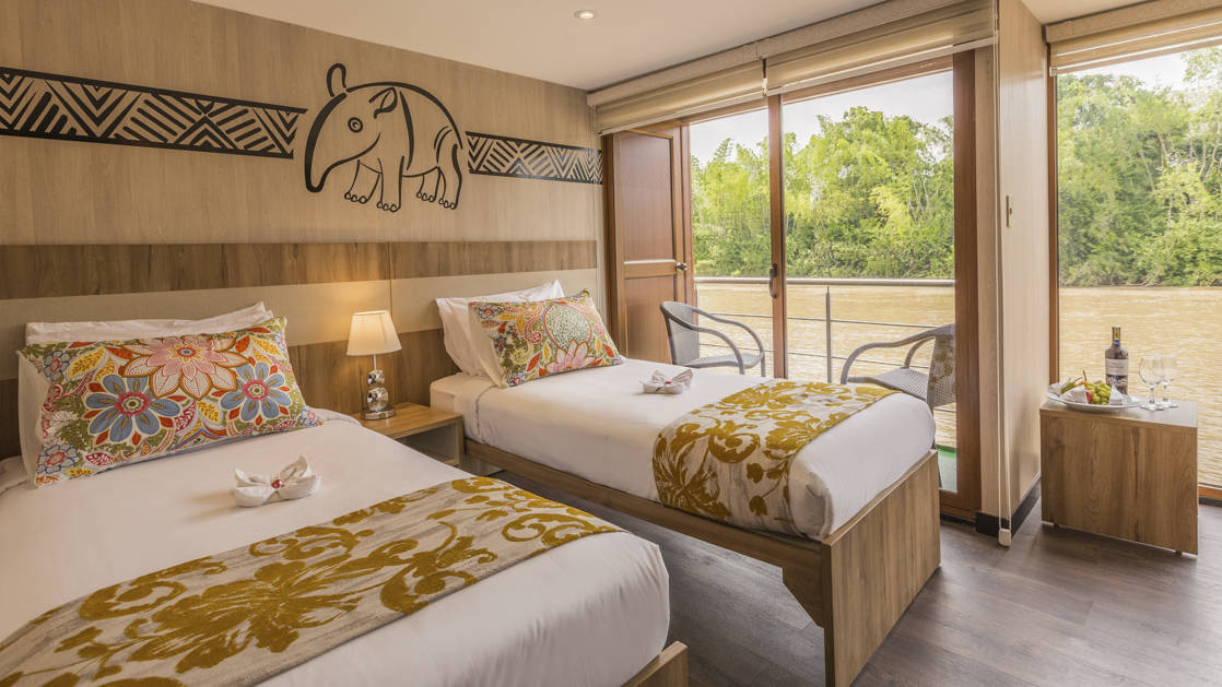 Standard Twin aboard Manatee Amazon Explorer with floor to ceiling windows, sliding glass door out to a private balcony, nightstand and reading lights.
