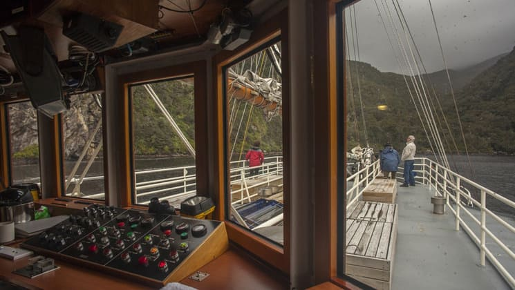 Milford Wanderer bridge view of the bow of the boat with passengers enjoying the mountains of New Zealand from the railing.