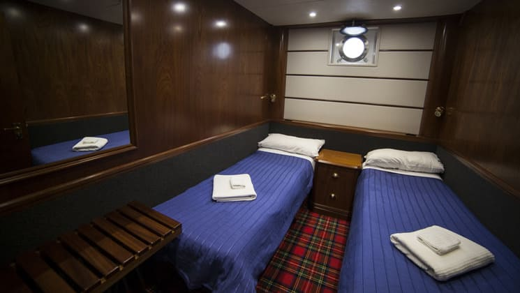 Milford Wanderer cabin with 2 twin beds, single porthole, with desk, nightstand and 2 reading lights.