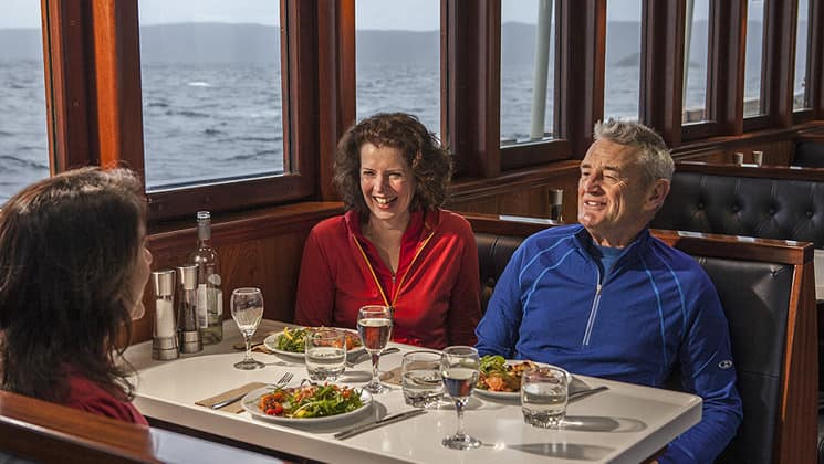 Milford Wanderer dining room with happy passengers enjoying a meal with large windows in New Zealand.