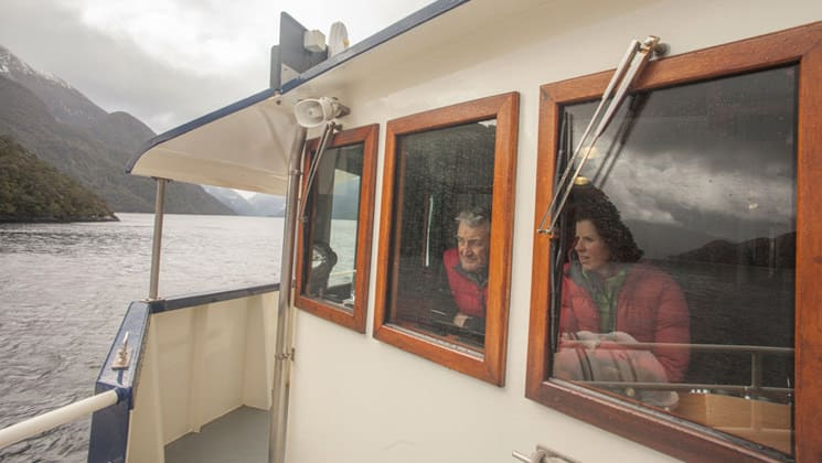 Milford Wanderer passengers looking out the window of the bridge while it's raining as the vessel sails through a fjord in New Zealand.