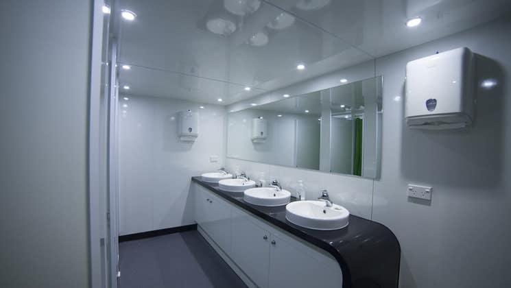 Milford Wanderer shared bathroom with vanity, multiple sinks, large mirror and showers.