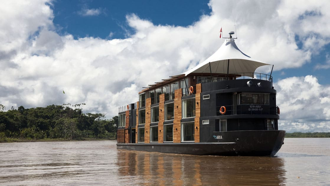 Aria cruising in the Amazon close to lush green land.