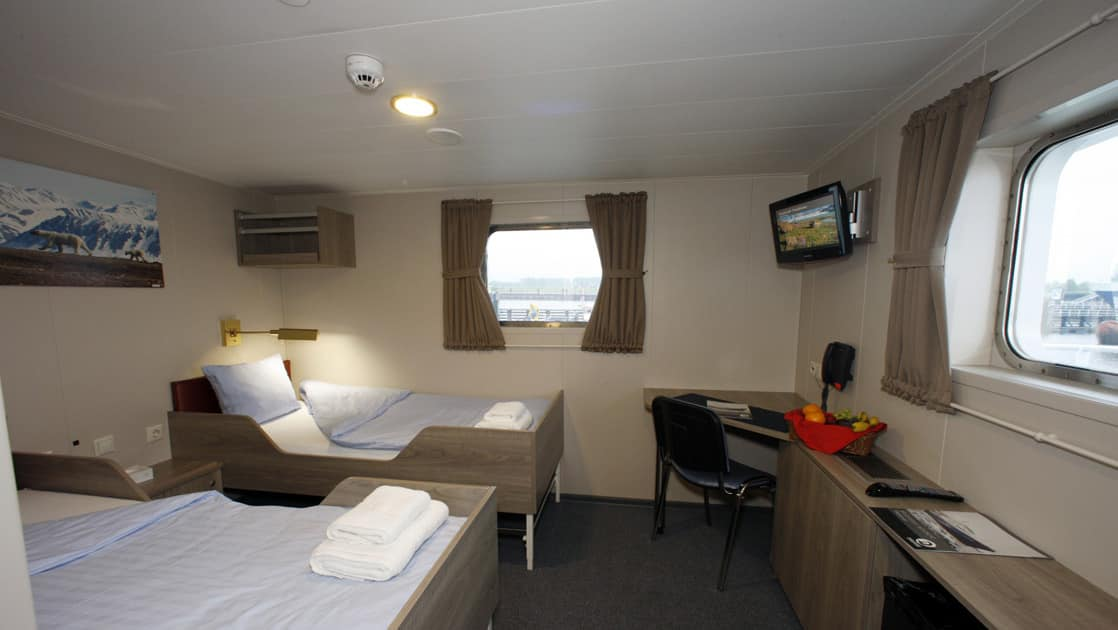 Twin Deluxe cabins with 2 windows and a table aboard Plancius Antarctica vessel