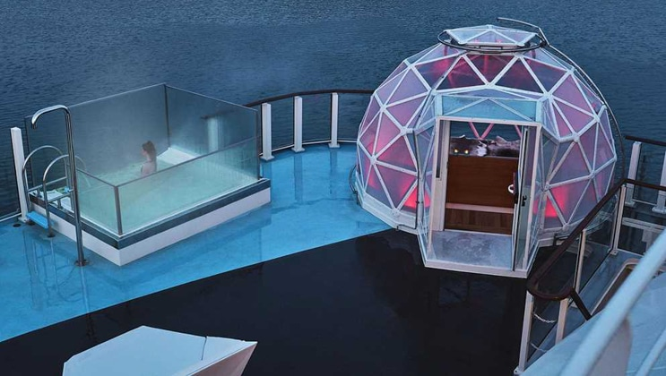 Glass geodesic dome with purple interior lighting sits beside a glass-walled small pool on deck of National Geographic Endurance.