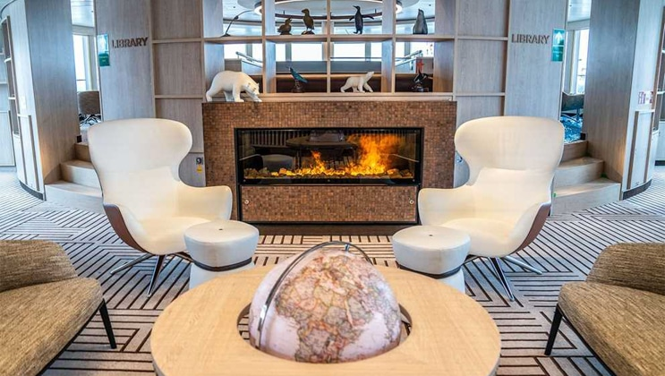 2 modern, white wingback chairs sit empty beside a coffee table with globe in front of a gas fireplace on National Geographic Endurance.