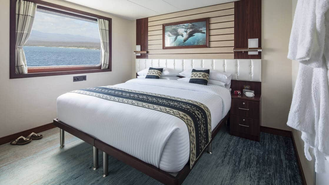 Cabin with large bed beside large picture window aboard Cabin with large bed, armchair, large window aboard National Geographic Endeavour II in the Galapagos Islands