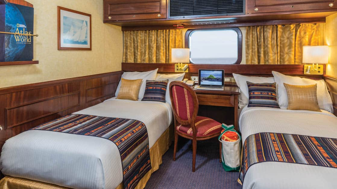 Two beds, desk, chair and window in cabin aboard National Geographic Islander expedition ship in Galapagos Islands