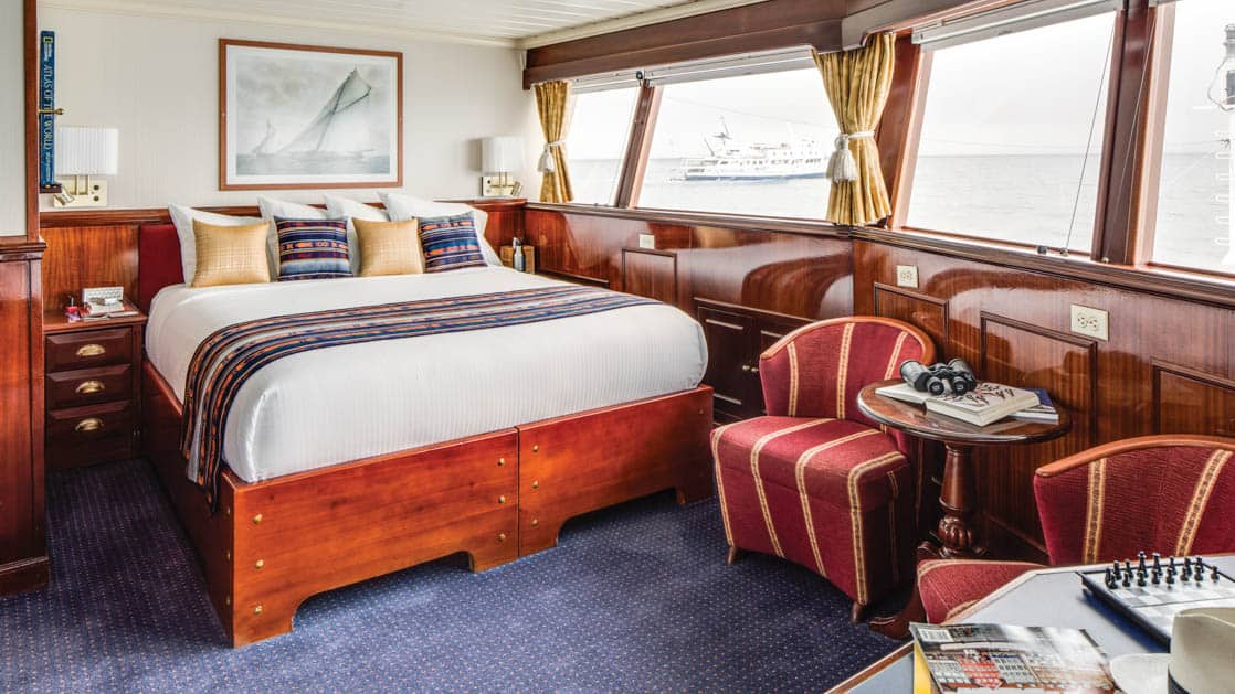 Large bed, desk, small table, two chairs and large windows of cabin aboard National Geographic Islander expedition ship in Galapagos Islands
