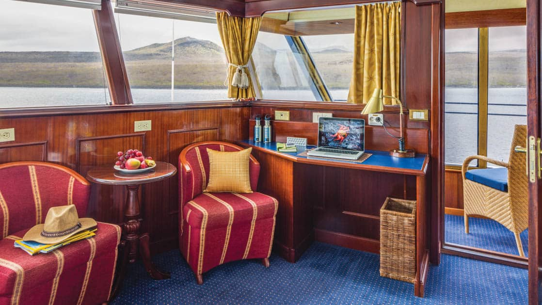 Cabin interior with desk, table, two chairs and private balcony aboard National Geographic Islander in Galapagos Islands