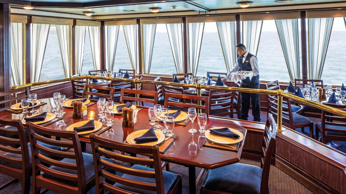 Crew member setting tables in dining room with window-lined walls aboard National Geographic Islander in Galapagos Islands