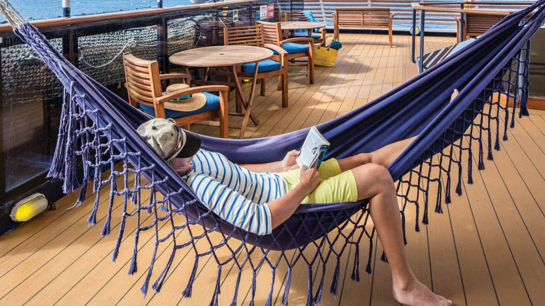 Woman reading in hammock on sunny deck of National Geographic Islander expedition ship in Galapagos Islands
