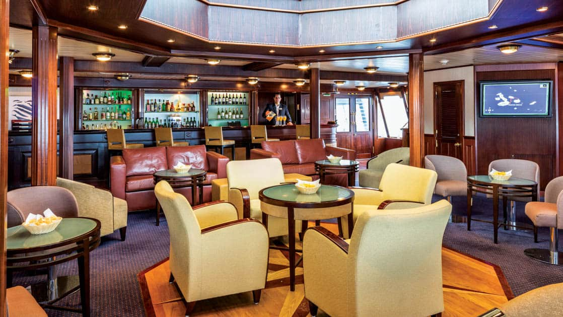 Couches, tables and chairs in lounge and bar aboard National Geographic Islander expedition ship in Galapagos Islands