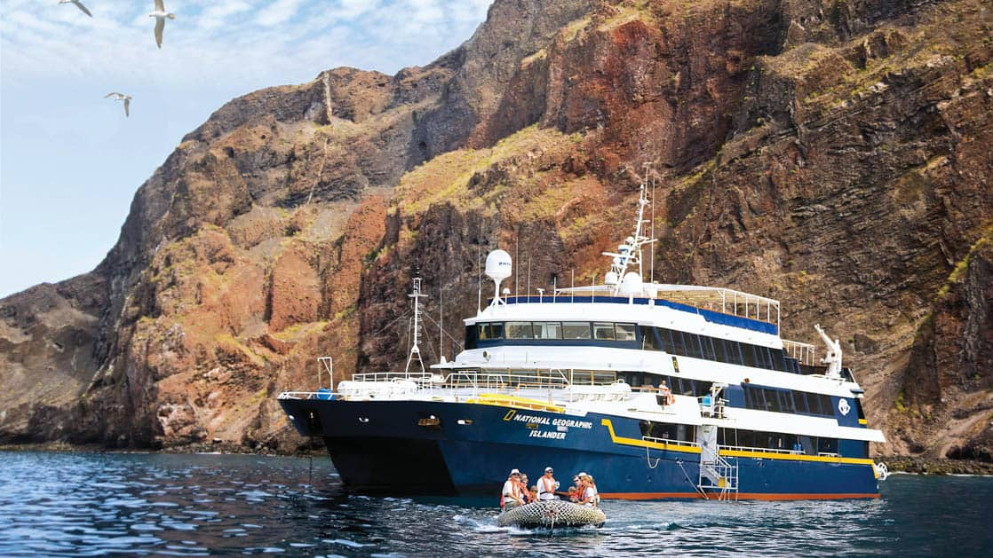 Full exterior of port side and bow of National Geographic Islander expedition ship with passengers on zodiac in Galapagos Islands