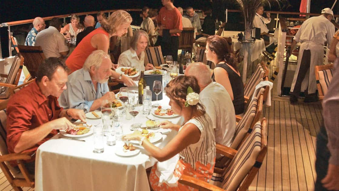 Guests dining at outdoor tables at night aboard National Geographic Orion expedition ship