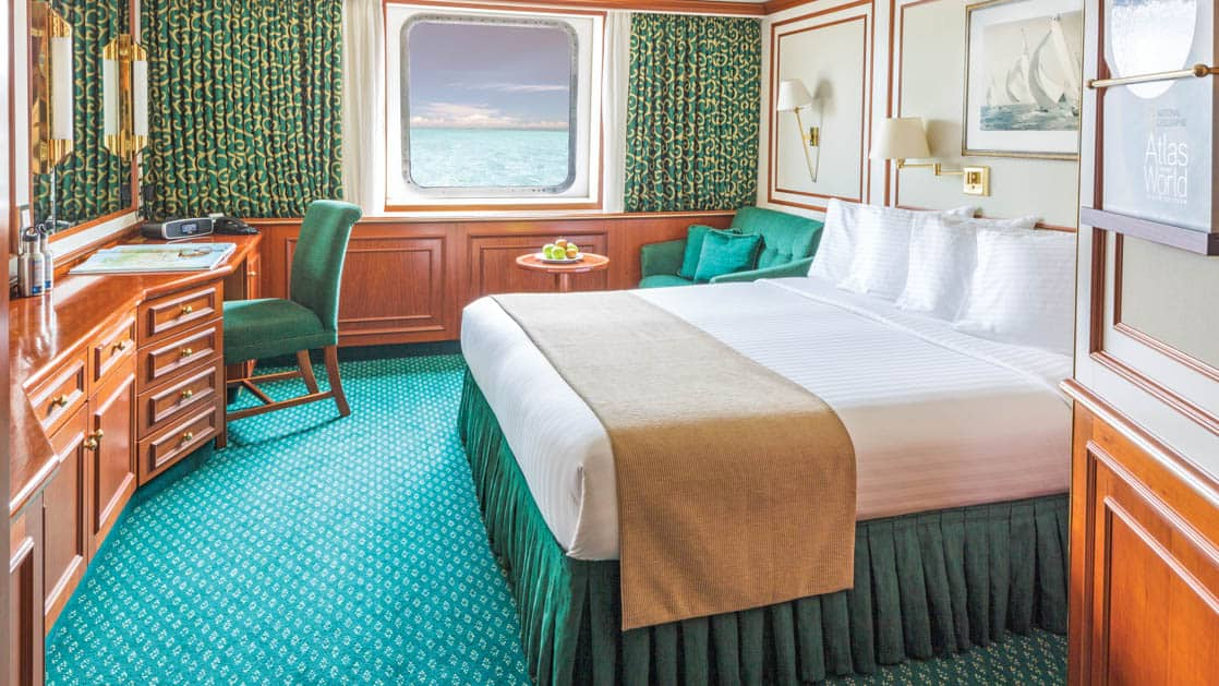 Category 3 cabin with large bed, corner armchair, desk, chair, small table and large window aboard National Geographic Orion expedition ship