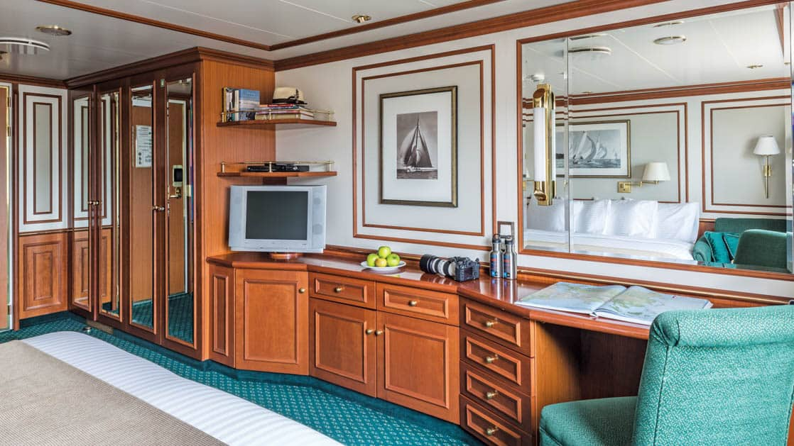 Large bed, desk, chair, TV and closet in Category 3 cabin aboard National Geographic Orion expedition ship