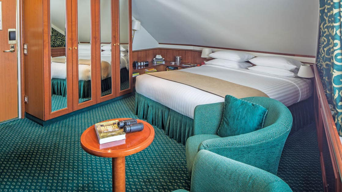 Category 3 cabin with large bed, closet, two armchairs and small table aboard National Geographic Orion expedition ship