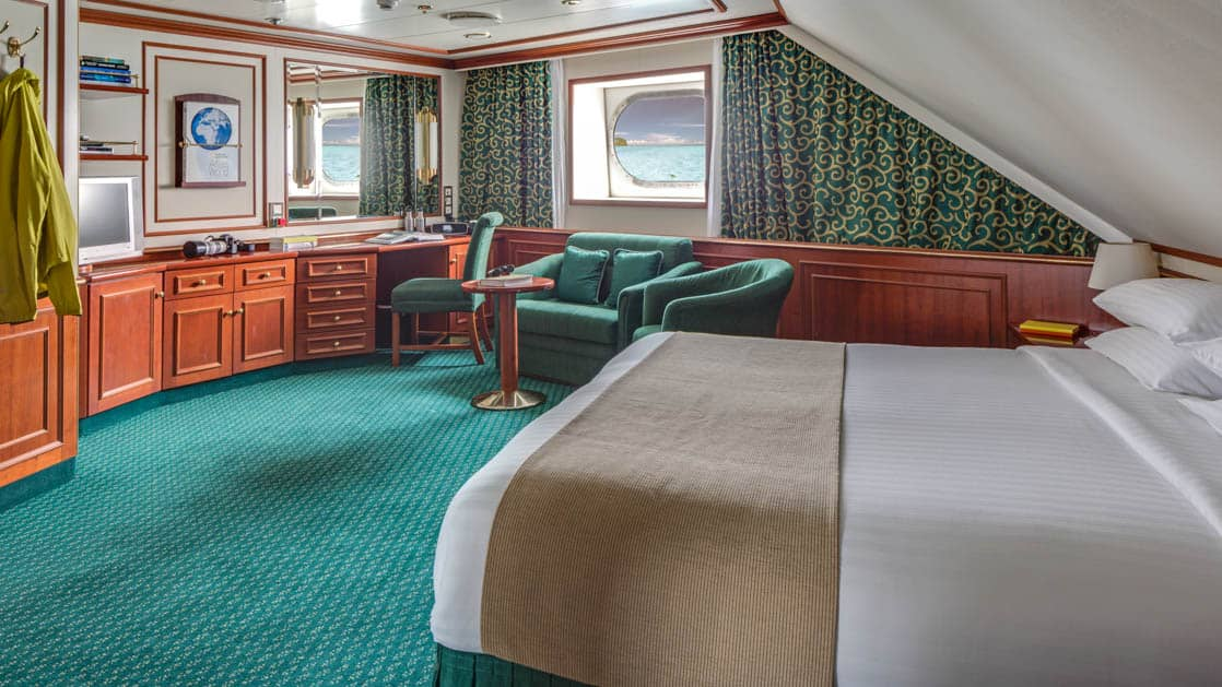 Category 3 cabin with large bed, two armchairs, small table, desk, chair and oval window aboard National Geographic Orion expedition ship