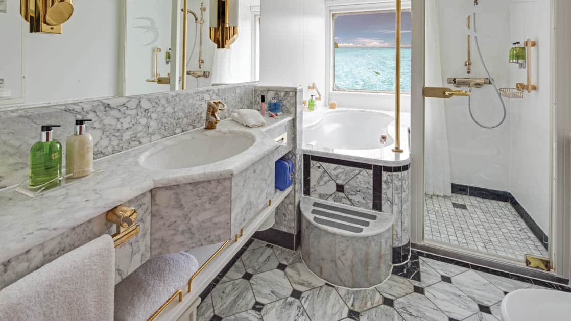 Shower, Jacuzzi, sink, mirror, toilet and large window in bathroom of Category 6 cabin aboard National Geographic Orion expedition ship
