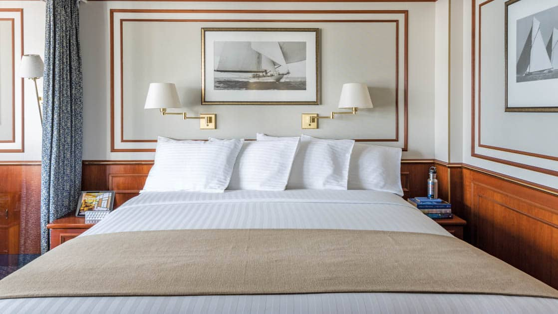 Large bed with two bedside tables and two reading lamps in Category 6 cabin aboard National Geographic Orion expedition ship
