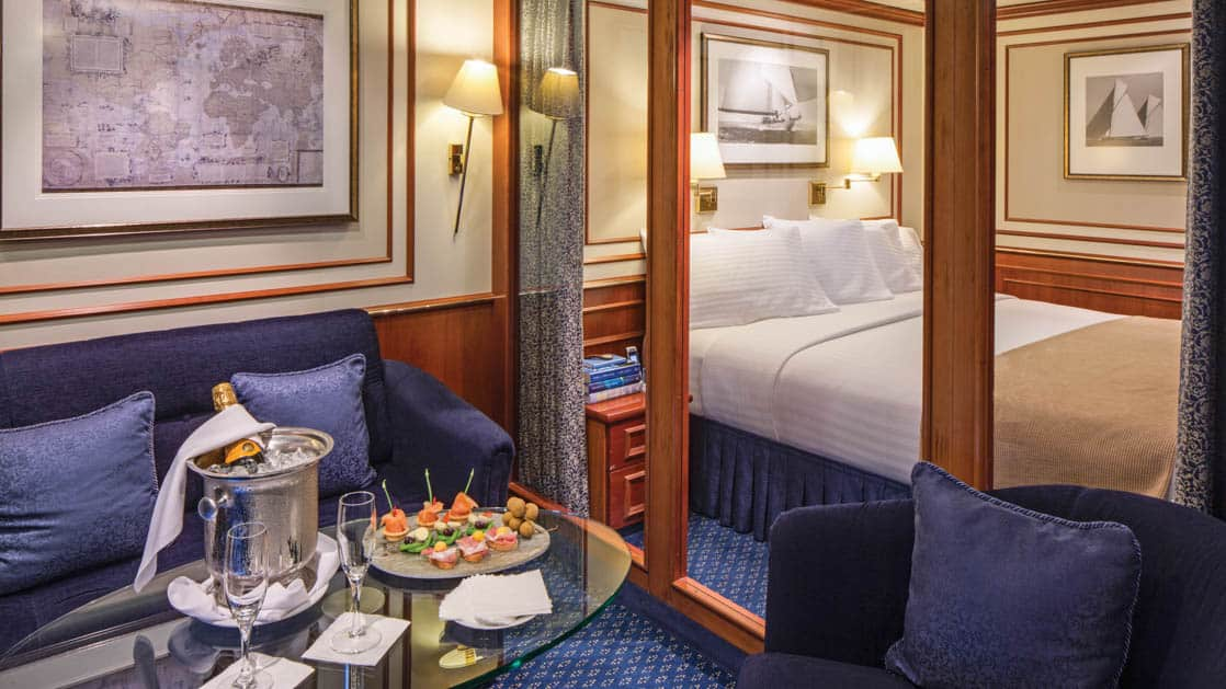Category 6 cabin interior with bed, couch, coffee table and armchair aboard National Geographic Orion expedition ship