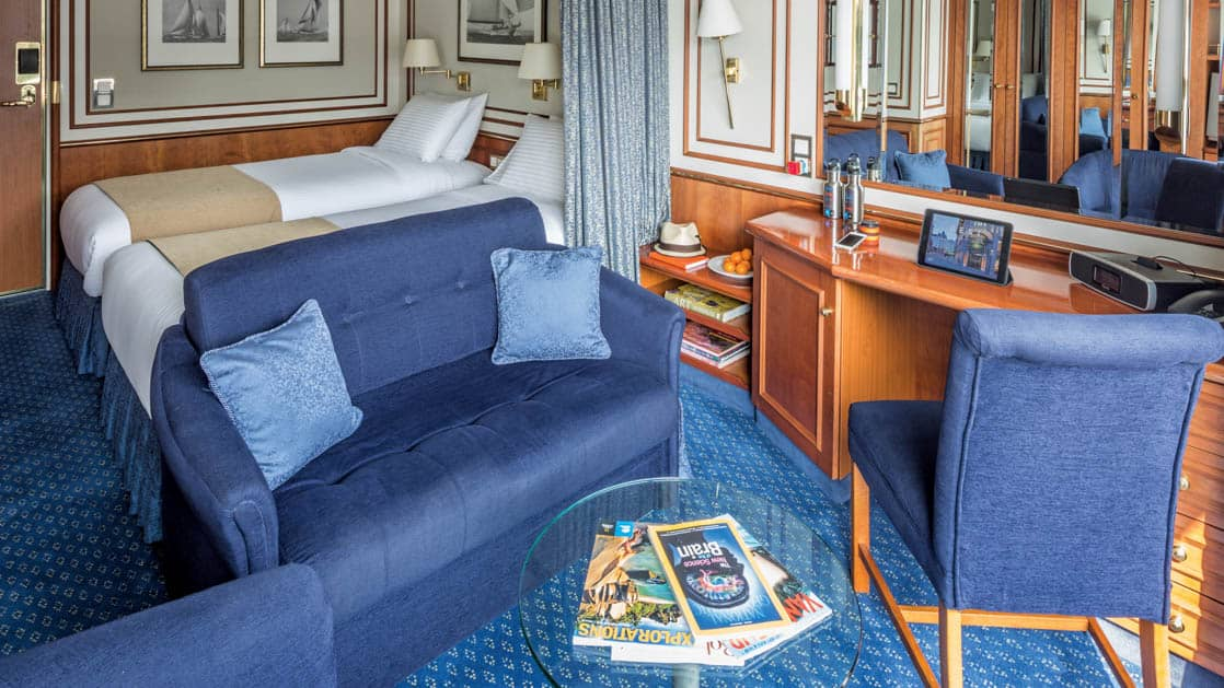 Two beds, couch, armchair, desk and chair in Category 5 cabin aboard National Geographic Orion expedition ship