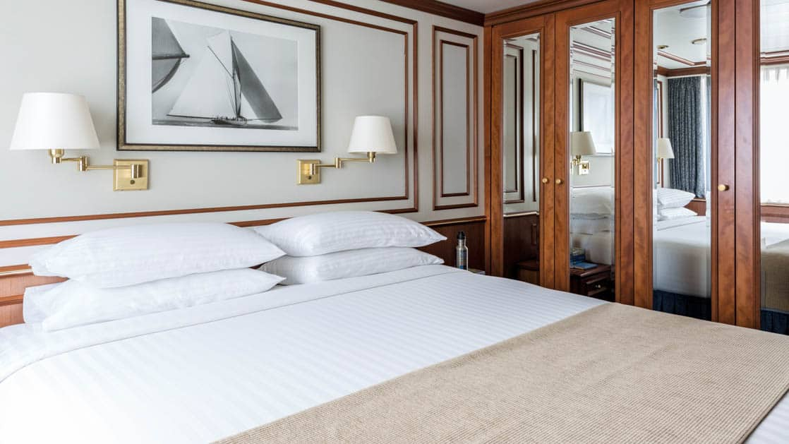 Large bed, closet and large window in Category 6 cabin aboard National Geographic Orion expedition ship