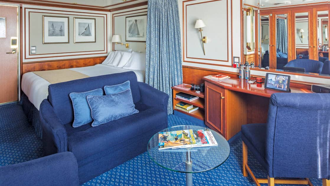 Category 4 cabin with large bed, couch, coffee table, desk and two chairs aboard National Geographic Orion expedition ship