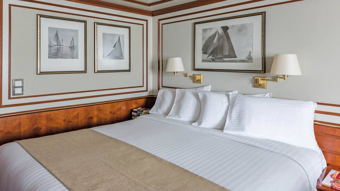Large bed in well-lit Category 4 cabin aboard National Geographic Orion expedition ship
