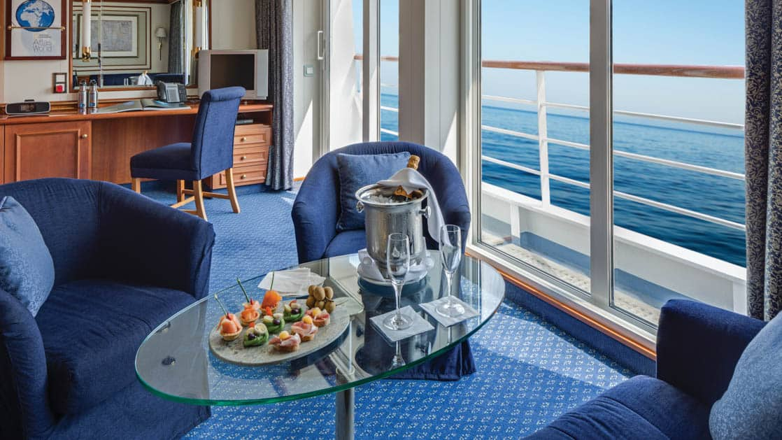 Sitting area with couch, coffee table and two armchairs with desk, chair and private balcony aboard National Geographic Orion expedition ship