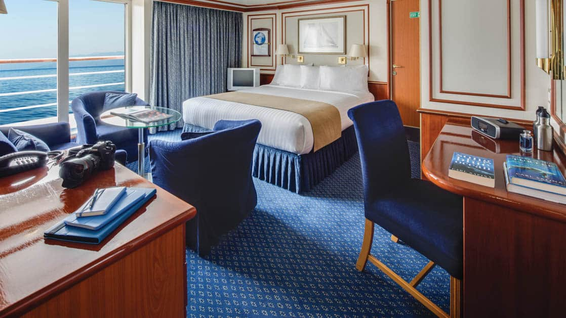 Cabin with couch, armchair, coffee table, desk, chair, two beds aboard National Geographic Orion expedition ship