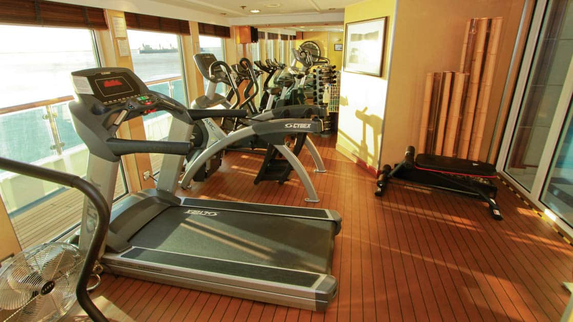 Exercise machines placed along floor-to-ceiling windows in the gym aboard National Geographic Orion expedition ship