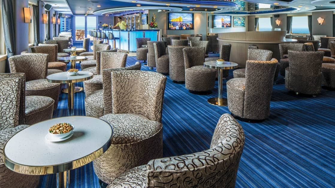 Tables and chairs set up by the windows with bar in background of lounge aboard National Geographic Orion expedition ship