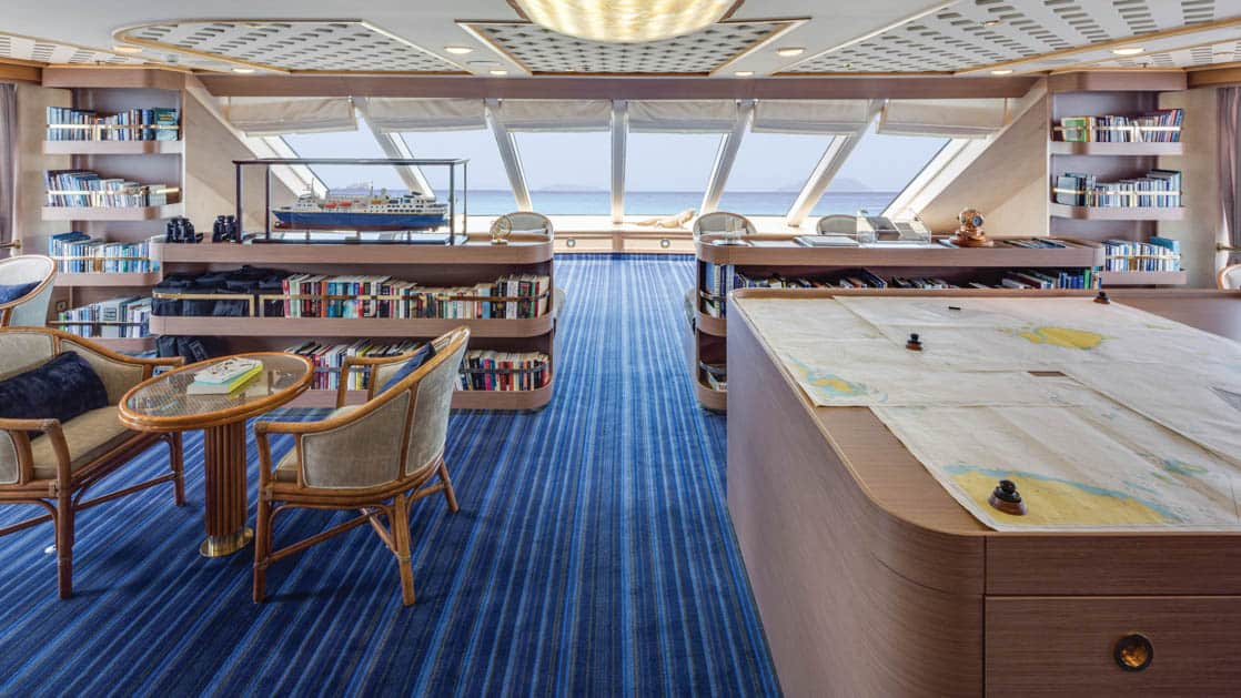 Observation lounge and library with charts on large table and seating areas aboard National Geographic Orion expedition ship